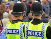 Two British policemen watching during crowded street event
