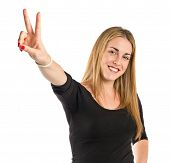 Blonde Girl Doing Victory Gesture Over White Background