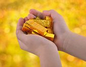 Gold ingots in the child's hand.
