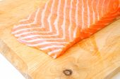 piece of fresh raw salmon on wooden tray isolated on white background