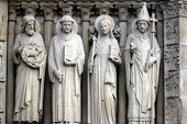 PARIS,FRANCE - NOV 05, 2012: St John the Baptist, St Stephen, St Genevieve and Pope St Sylvester, detail of Notre Dame cathedral. The Portal of the Virgin, dedicated to the patroness of the cathedral.