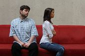 image of hope  - sad couple sitting on a red sofa - JPG