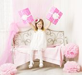 Girl Holding  Birthday Presents. Happy Child With Party Gift Boxes In Pink Color