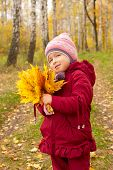 Little girl with yellow leaves in forest