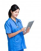 Asian doctor woman look at digital tablet