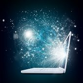 Open laptop with magic light and falling stars