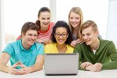 education, technology and college concept - five smiling students looking at laptop at school