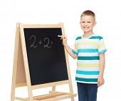 people, childhood, mathematics and education concept - happy little boy with blackboard and chalk wr