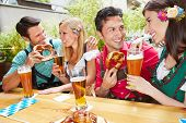 Men and women flirting in bavarian beer garden in summer
