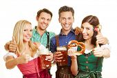 Group of friends holding thumbs up in Bavaria with beer and pretzel