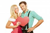 Happy couple in Bavaria in dirndl and leather pants with a red heart
