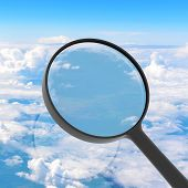 Magnifying glass looking clouds in background