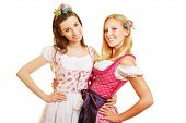 Two happy women in pink dirndl dress in Bavaria at Oktoberfest