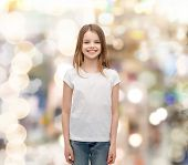 advertising and t-shirt design concept - smiling little girl in white blank t-shirt over white backg