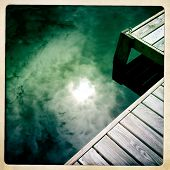 Instagram style image of the sun and clouds reflecting in a lake by a boardwalk