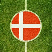 Football field center closeup with Danish flag in circle