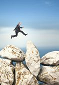 businessman jump over huge rock