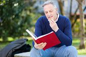 Mature man reading a book at the park