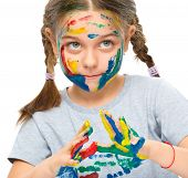 Portrait of a cute girl looking at her hands painted in bright colors, isolated over white