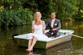 stock photo of ponds  - beautiful young wedding couple blonde bride with flower and her groom just married on small boat at pond with evening sun - JPG