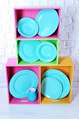 Beautiful  bright shelves and boxes with tableware  on  light wall background