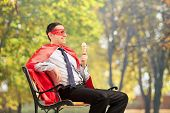 Superhero enjoying an ice cream seated on bench in park