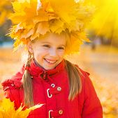 Smiling cute little girl among autumn  maple leaves