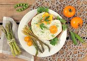 eggs with asparagus on wooden table