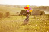 Happy Young Woman With Balloons Among A Field