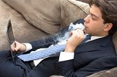 Businessman Relaxing On A Sofa Smoking And Working
