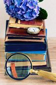 pile of old books with flowers and clock