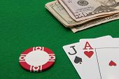 Blackjack hand with Dollar notes and chip on green background