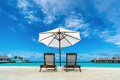 Beach lounger and umbrella on sand beach. Concept for rest, relaxation, holidays, spa, resort.