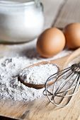 flour, eggs and kitchen utensil on a wooden board