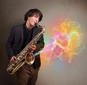image of saxophone player  - Attractive young musician playing on saxophone with colorful abstract fume comming out - JPG