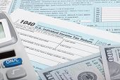 image of cpa  - Tax Form 1040 with calculator and 100 US dollar bills - JPG