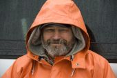 foto of clam digging  - Bearded fisherman in orange rain slicker on Washington coast - JPG
