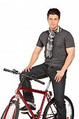 Man with scarf posing seated on a bicycle isolated on white background