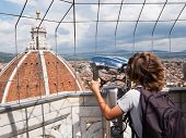 Tourism concept: boy looking through a sightseeing binoculars the Dome of Basilica di Santa Maria de
