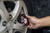Checking tires with a hand held tire pressure gauge