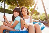 Two Girls Having Fun On Swing In Playground