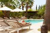 Woman Relaxing On Sun Lounger By Hotel Swimming Pool