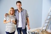 Portrait Of Couple Decorating Nursery For New Baby