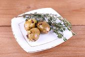 Green olives in oil with spices and rosemary on plate on wooden table