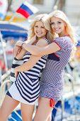 Two beautiful young women relaxing on the pier near the marina.