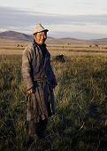 Mongolian milking man standing in a scenic view of the field.