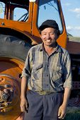 picture of mongolian  - Smiling Mongolian farmer standing next to the tractor - JPG