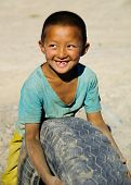 Asian boy with a beautiful smile playing with a tyre.