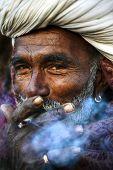 Indigenous Indian man smoking happily.
