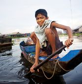 Boy traveling by boat in floating village.